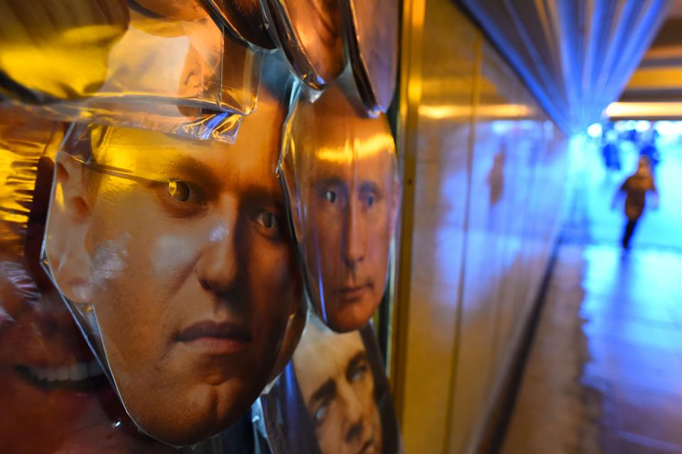 <p>Masks of opposition leader Alexei Navalny and President Vladimir Putin are seen on sale at a souvenir stall in an underground passage in Saint Petersburg </p> (AFP/Getty)