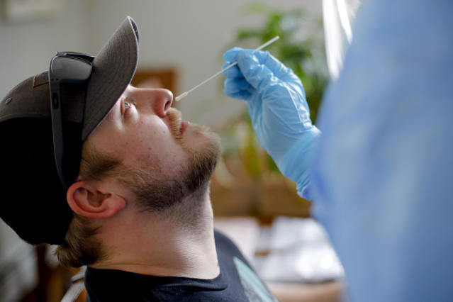 """FILE - In this April 21, 2020, file photo, BFAIR shared living home staff member Matthew Donahue receives a COVID-19 swab test in Pittsfield, Mass. At a cost of $120-130 per test, and NHL Commissioner Gary Bettman's estimate the league will need 25,000-35,000 in total to get through the playoffs, the price tag he concedes is """"millions of dollars."""" But regular testing is something players insisted on in the name of feeling safe to compete. (Stephanie Zollshan/The Berkshire Eagle via AP, File)"""