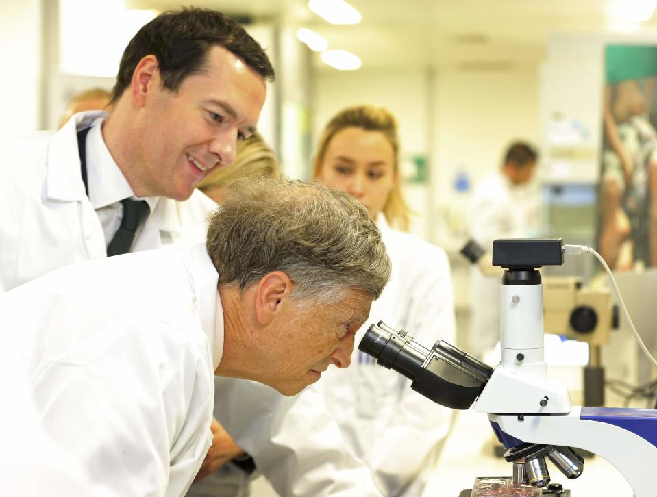 Microsoft co-founder Bill Gates looks through a microscope during a tour with Britain's Chancellor George Osborne (L) to the Liverpool School of Tropical Medicine in Liverpool, Britain January 25, 2016. Britain will spend 500 million pounds ($700 million) per year for the next five years to try and end deaths caused by malaria, the government said on Monday, announcing a partnership with Gates worth a total of 3 billion pounds. REUTERS/Dave Thompson/pool