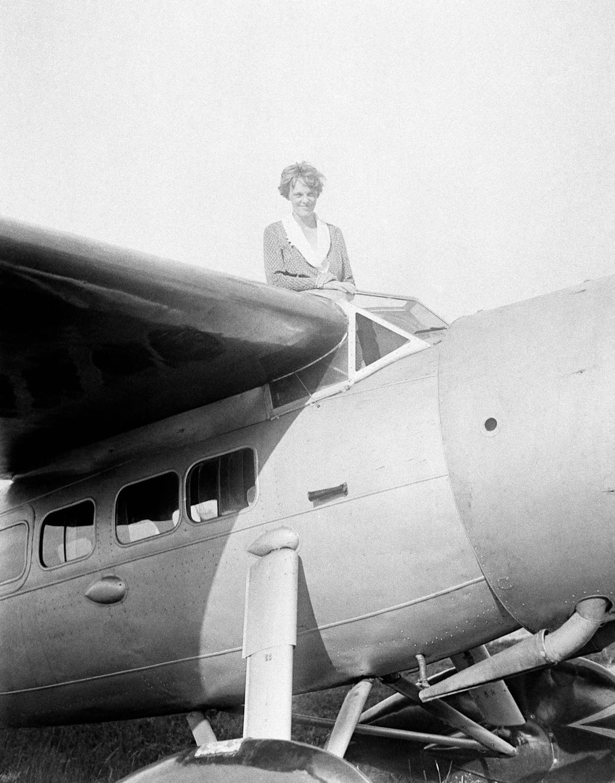 FILE - In this undated photo, Amelia Earhart, the first woman to cross the Atlantic Ocean by plane sits on top of a plane. Secretary of State Hillary Rodham Clinton is wading into one of the 20th century's most enduring mysteries: the fate of American aviator Amelia Earhart, disappeared over the South Pacific 75 years ago. Clinton is meeting March 20, 2012, with historians and scientists from The International Group for Historic Aircraft Recovery, which will launch a new search in June for the wreckage of Earhart's plane off the remote island of Nikumaroro. (AP Photo)