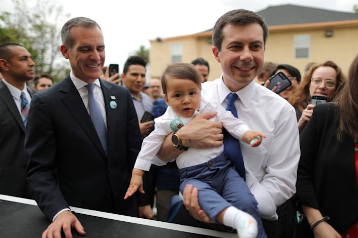 Democratic presidential candidate Pete Buttigieg, right, holds a baby as he campaigns with Los Angeles Mayor Eric Garcetti in Los Angeles, May 9. (Photo: Lucy Nicholson/Reuters)