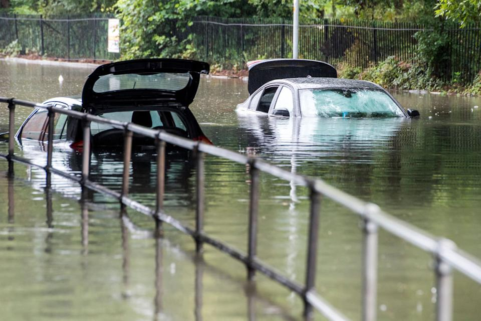 Cars rapped in flood water under a bridge on Crossley Road near Levenshulme (Picture: Getty)