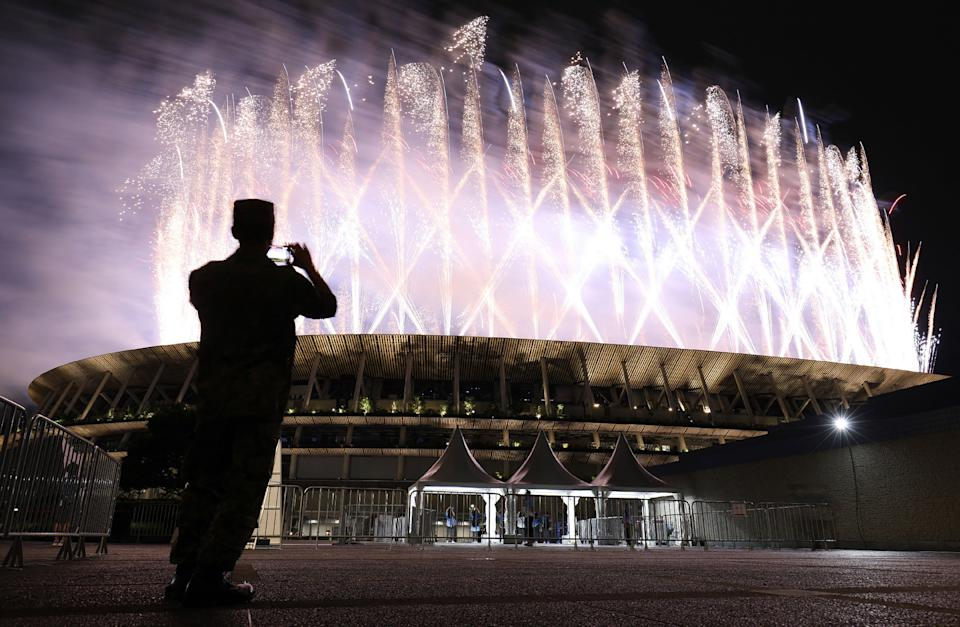 <p>A man takes pictures of the fireworks lighting up the sky over the Olympic Stadium during the opening ceremony of the Tokyo 2020 Olympic Games. (Photo by STR/JIJI PRESS/AFP via Getty Images)</p>