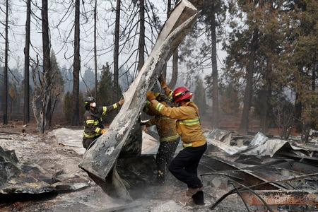FILE PHOTO: Firefighters move debris while recovering human remains from a trailer home destroyed by the Camp Fire in Paradise, California, U.S., November 17, 2018.  REUTERS/Terray Sylvester