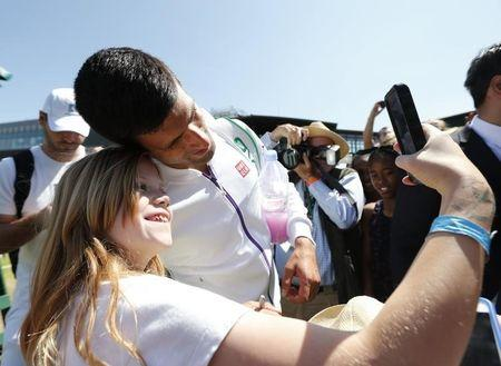 Novak Djokovic of Serbia takes a selfie with a fan after a practice session at the Wimbledon Tennis Championships in London