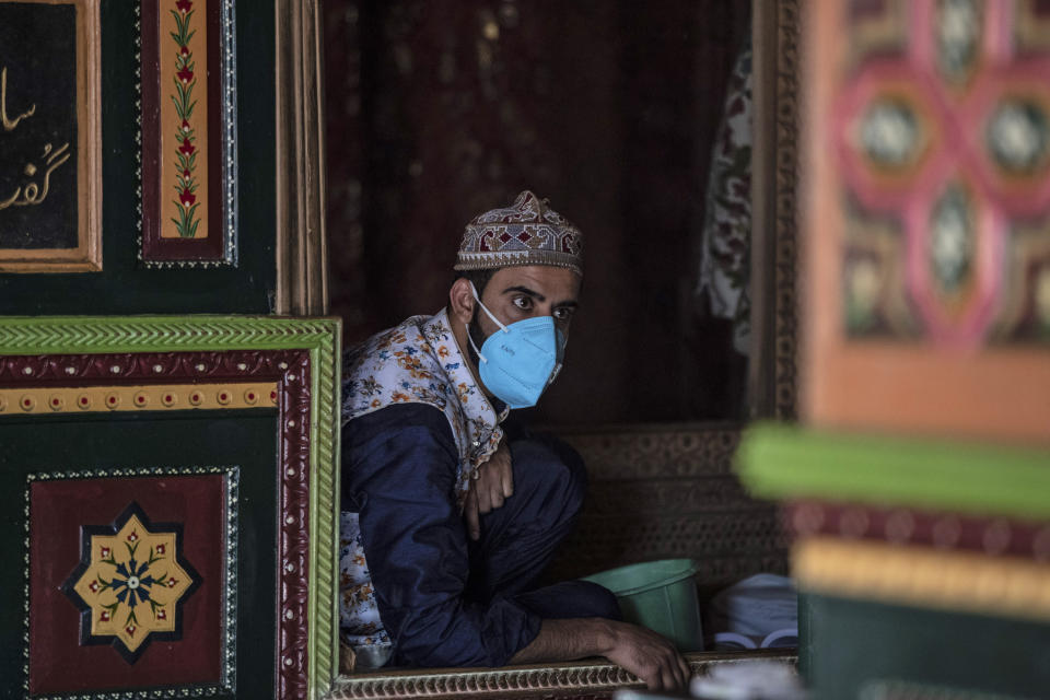A Kashmiri priest wearing a wearing a face mask as a precautionary measure against the coronavirus sits inside a muslim shrine in Srinagar, Indian-controlled Kashmir, Saturday, Oct. 3, 2020. India has crossed 100,000 confirmed COVID-19 deaths on Saturday, putting the country's toll at nearly 10% of the global fatalities and behind only the United States and Brazil. (AP Photo/Mukhtar Khan)