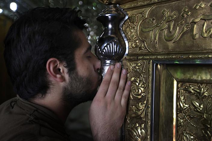 A Shiite Iranian man kisses the grave of Saint Ali Akbar shrine, in northern Tehran, Iran, Sunday, June 23, 2013. Hatreds between Shiites and Sunnis are now more virulent than ever in the Arab world because of Syria's brutal civil war. Hard-line clerics and politicians on both sides have added fuel, depicting the fight as essentially a war of survival for their sect. (AP Photo/Vahid Salemi)