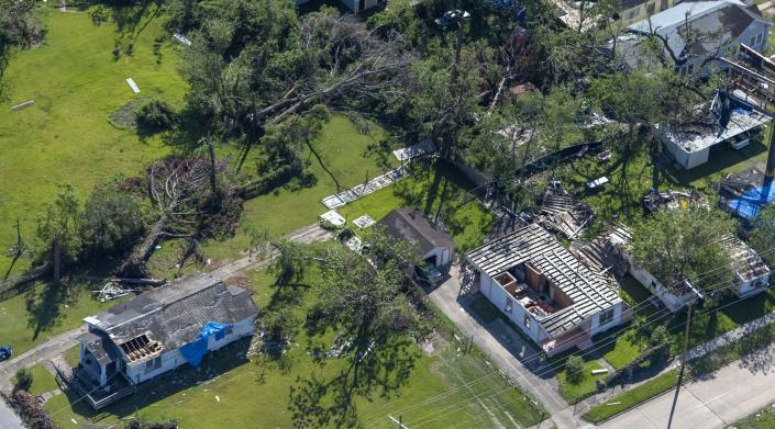 Fallen trees, roof destruction and blue tarps as seen in the aftermath of Hurricane Delta Saturday Oct. 10, 2020, in Iowa, La. (Bill Feig/The Advocate via AP, Pool)