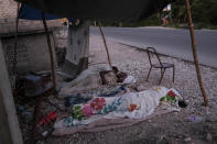 """Nurse Gabrielle Lagrenade, center, sleeps next to her daughter on the the side of the road in Les Cayes, Haiti, Monday, Aug. 23, 2021, a week after a 7.2 magnitude earthquake made her rental home unsafe to live in. Lagrenade, 52, describes her current living conditions simply as """"inappropriate,"""" but she continues arriving for her daily shift at the hospital. (AP Photo/Matias Delacroix)"""