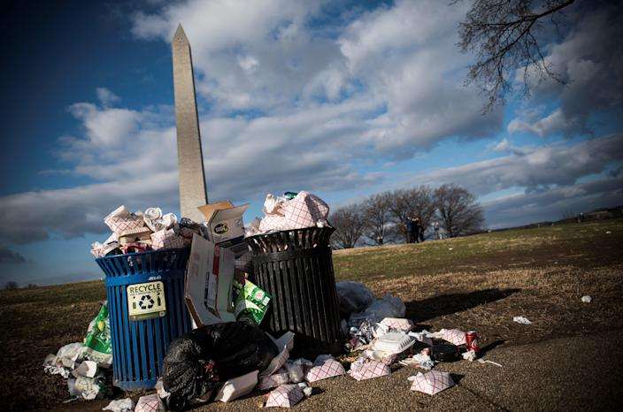 Litter spills out of a public dustbin next to the Washington Monument on the National Mall in Washington DC on December 24, 2018.  (Photo by Eric BARADAT/AFP/Getty Images)