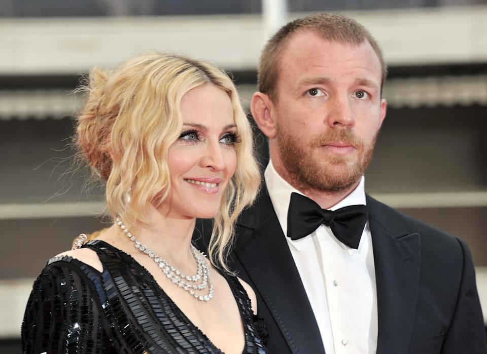 """US singer Madonna (L) and her husband British director Guy Ritchie pose as they arrive to attend the screening of Nathan Rissman's film 'I Am Beacuse We Are' at the 61st Cannes International Film Festival on May 21, 2008 in Cannes, southern France. The May 14-25 festival winds up with the awards ceremony for the prestigious Palme d'Or, to be determined by a jury headed by Hollywood """"bad boy"""" Sean Penn.       AFP PHOTO / ANNE-CHRISTINE POUJOULAT        (Photo credit should read ANNE-CHRISTINE POUJOULAT/AFP/GettyImages)"""