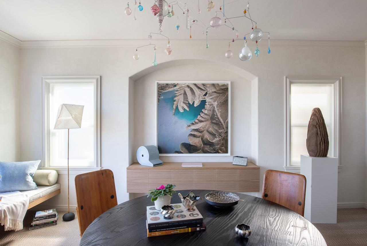 The beauty and tranquility of the Marin Headlands, as seen through the room's picture window, informed David Bjørngaard's design. A modern BDDW walnut dining table is surrounded by vintage Axel Einar Hjorth Lovo Dining Chairs from Almond & Co. A custom rug by Kyle Bunting lays beneath.