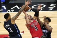 Chicago Bulls center Nikola Vucevic, center, shoots as Orlando Magic forward Chuma Okeke, left, and center Wendell Carter Jr. defend during the second half of an NBA basketball game in Chicago, Wednesday, April 14, 2021. (AP Photo/Nam Y. Huh)