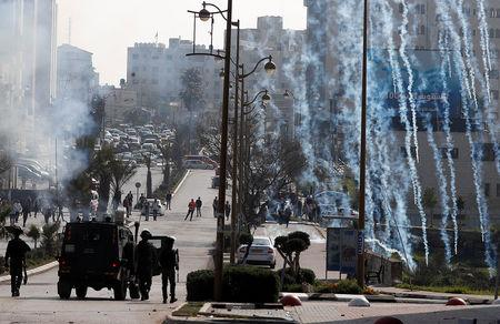 Israeli forces fire tear gas canisters at Palestinian protesters during clashes near the Jewish settlement of Beit El, in the Israeli-occupied West Bank