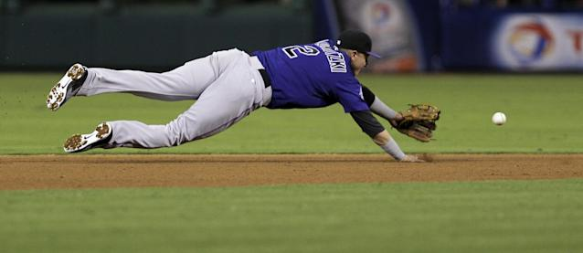 Colorado Rockies' Troy Tulowitzki lunges for a base hit by Philadelphia Phillies' Domonic Brown in the fourth inning of a baseball game, Monday, Aug. 19, 2013, in Philadelphia. (AP Photo/Laurence Kesterson)