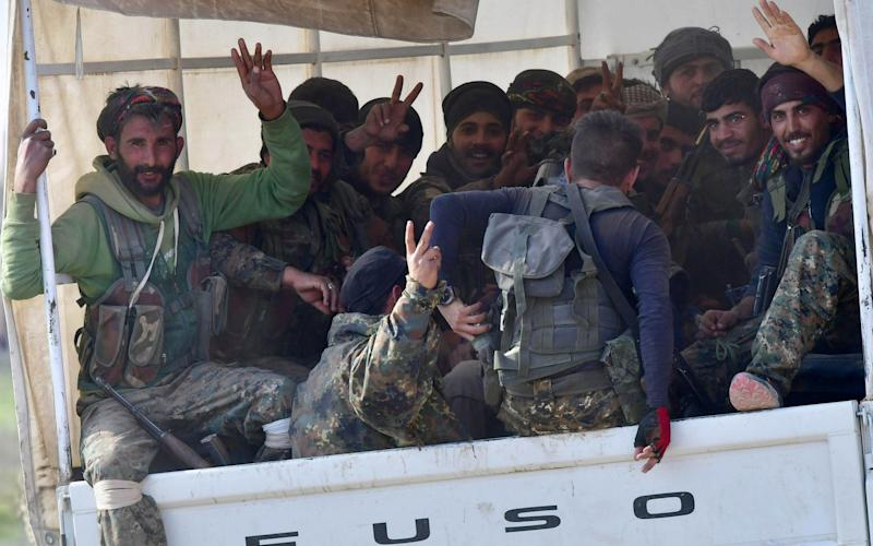 Fighters from the Syrian Democratic Forces (SDF) gesture the