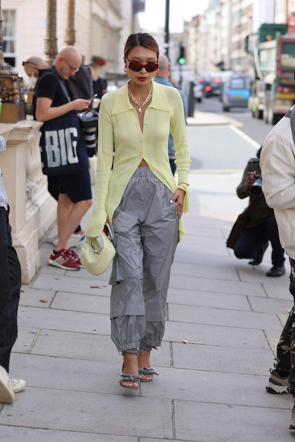"""Grey cargo pants and a lemony, light-weave knit is giving us <a href=""""https://www.refinery29.com/en-gb/autumn-transitional-office-wear-clothing"""" rel=""""nofollow noopener"""" target=""""_blank"""" data-ylk=""""slk:back-to-work wardrobe"""" class=""""link rapid-noclick-resp"""">back-to-work wardrobe</a> inspo.<span class=""""copyright"""">Photo Courtesy of Neil Mockford/Getty Images.</span>"""