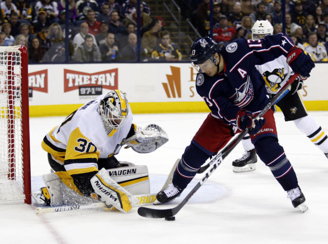 Columbus Blue Jackets forward Cam Atkinson, right, settles the puck in front of Pittsburgh Penguins goalie Matt Murray during the second period of an NHL hockey game in Columbus, Ohio, Saturday, March 9, 2019. (AP Photo/Paul Vernon)