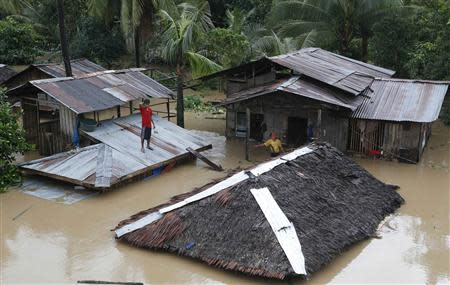 """A resident stands on the roof of his home that is submerged in heavy flooding brought by tropical depression """"Agaton"""", in Butuan city"""