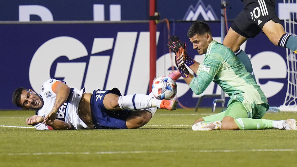 Los Angeles Galaxy goalkeeper Jonathan Bond, right, makes a save against Vancouver Whitecaps forward Lucas Cavallini, right, in the second half during an MLS soccer match Wednesday, June 23, 2021, in Sandy, Utah. (AP Photo/Rick Bowmer)