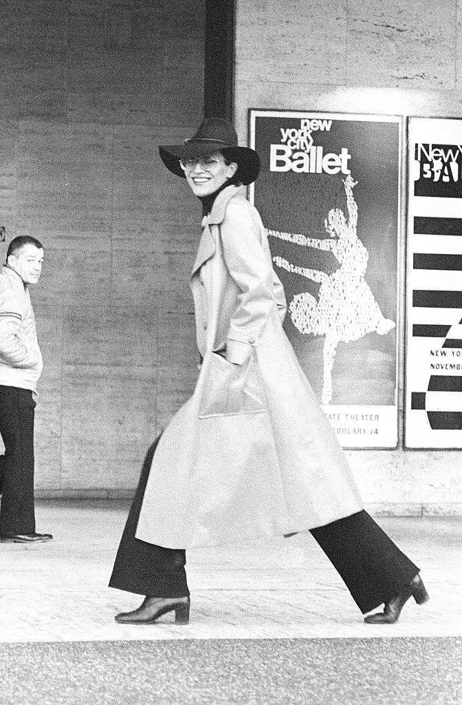 <p> Model Elsa Peretti wearing wide-leg pants with a long-length trench circa 1950. </p>