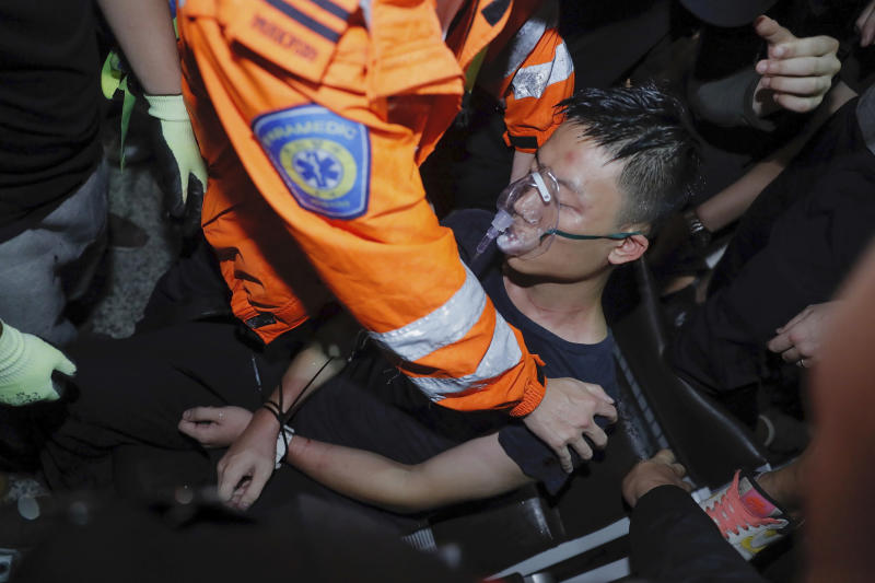 A medical staffer helps a detained man, who protesters claimed was a police officer from mainland China, during a demonstration at the Airport in Hong Kong, Tuesday, Aug. 13, 2019. Protesters severely crippled operations at Hong Kong's international airport for a second day Tuesday, forcing authorities to cancel all remaining flights out of the city after demonstrators took over the terminals as part of their push for democratic reforms. (AP Photo/Kin Cheung)