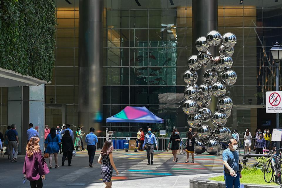 People walk along a promenade at the Raffles Place financial business district in Singapore.