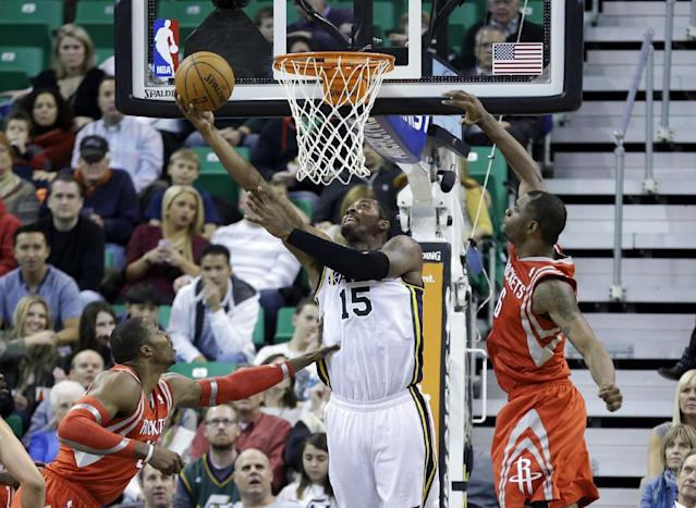 Utah Jazz's Derrick Favors (15) shoots as Houston Rockets' Dwight Howard, left, and teammate Terrence Jones defends in the second quarter of an NBA basketball game Monday, Dec. 2, 2013, in Salt Lake City. (AP Photo/Rick Bowmer)