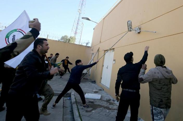 Iraqi protesters tear a security camera off a wall at the US embassy compound in Baghdad (AFP Photo/AHMAD AL-RUBAYE)