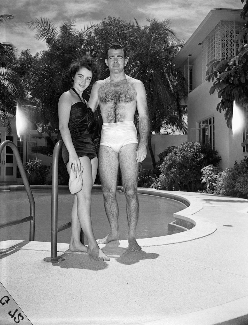 <p>A young Elizabeth Taylor and her then-fiancé William D. Pawley Jr. pose poolside at Pawley's family home in Miami, circa 1949. </p>