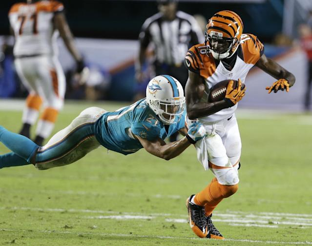 Miami Dolphins cornerback Brent Grimes (21) tackles Cincinnati Bengals wide receiver A.J. Green (18) during the second half of an NFL football game, Thursday, Oct. 31, 2013, in Miami Gardens, Fla. (AP Photo/Lynne Sladky)
