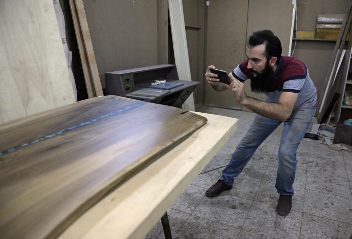 Ali Hedieloo takes a photo of his product to post on social media at his furniture workshop in the southern suburbs of Tehran, Iran, Friday, July 30, 2021. New legislation proposed by Iran's hard-line lawmakers that is designed to restrict access to social media applications in Iran has sent a wave of panic through society, stirring concerns among young Iranians, social media users and business owners. Like an estimated 1 million other Iranians, Hedieloo uses social media to find customers. (AP Photo/Vahid Salemi)
