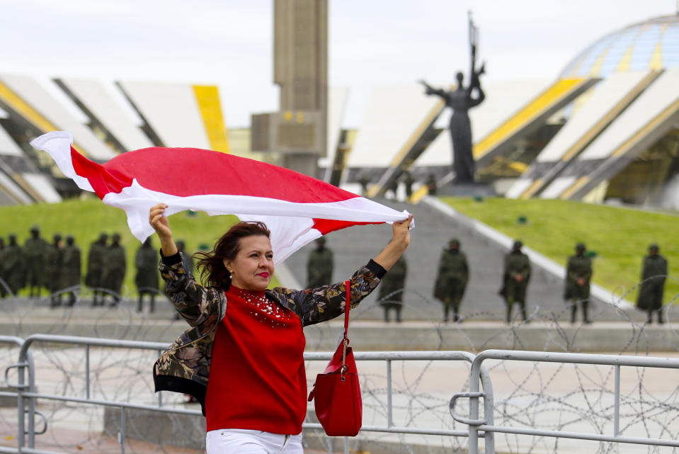 A woman waves an old Belarusian national flag as she a police line in front of a WWII memorial, during an opposition rally to protest the official presidential election results in Minsk, Belarus, Sunday, Sept. 27, 2020.Hundreds of thousands of Belarusians have been protesting daily since the Aug. 9 presidential election. (AP Photo/TUT.by)