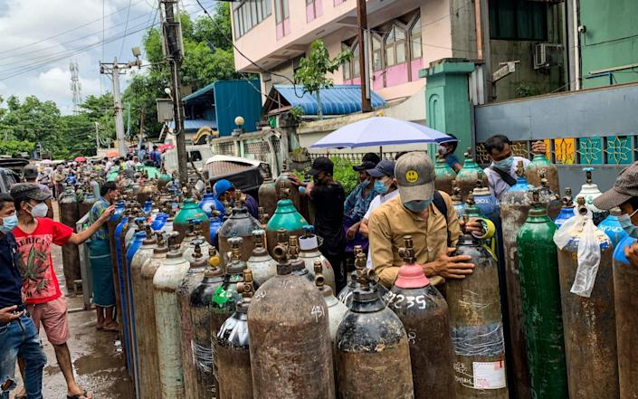 People stand with empty oxygen canisters as they wait to fill them up outside a factory in Yangon amid a surge in Covid-19 coronavirus cases. - YE AUNG THU/AFP