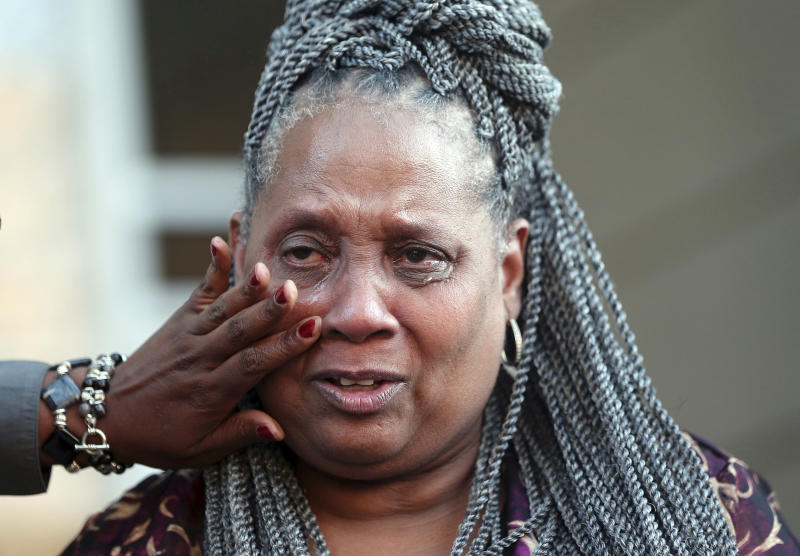 Wajeedah Jones, niece of Wilbert Jones, reaches to wipe away tears from Wilbert's sister-in-law, Wilda Jones, as family members and attorneys speak on the steps of state district court in Baton Rouge, La., Tuesday, Nov. 14, 2017. The Louisiana man who has spent nearly 50 years in prison will be freed after a judge overturned his conviction in the kidnapping and rape of a nurse. State District Court Judge Richard Anderson set Wilbert Jones' bail at $2,000 after hearing arguments from defense attorneys and prosecutors in a Baton Rouge courtroom. One of his lawyers expects him to be released Wednesday. Anderson threw out Jones' conviction on Oct. 31, saying authorities withheld evidence that could have exonerated Jones decades ago. (AP Photo/Gerald Herbert)