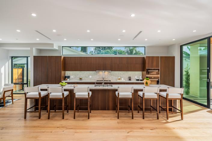 """<div class=""""caption""""> Chrissy Teigen and John Legend's new kitchen features an extremely long island. </div> <cite class=""""credit"""">Courtesy of Benjamin Illulian of Illulian Realty</cite>"""