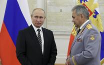 Russian President Vladimir Putin, left, listens to Defense Minister Sergei Shoigu during a meeting with senior military officers in Moscow, Russia, Wednesday, Nov. 6, 2019. Putin said Russia's new weapons have no foreign equivalents but he insists the country will not use them to threaten anyone. (Mikhail Klimentyev, Sputnik, Kremlin Pool Photo via AP)