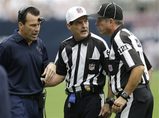 Houston Texans coach Gary Kubiak, left, discusses a play with referees Don King (60) and Curtis Townsend (121) in the first quarter of an NFL football game against the Miami Dolphins, Sunday, Sept. 9, 2012, in Houston. (AP Photo/David J. Phillip)