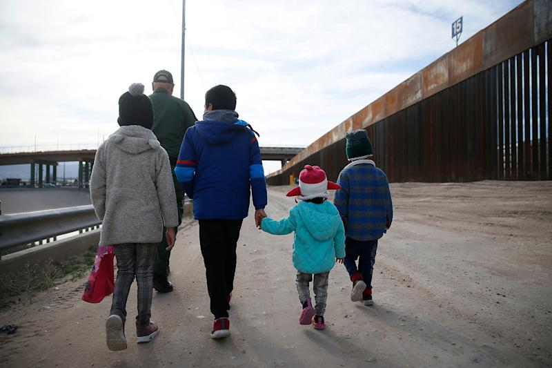 Border patrol agent Joe Romero escorts four unattended migrant children from Ecuador to another agent for transport Tuesday, Feb. 18, by the east bridge near Staton bride in El Paso. The children were waiting by the border fence on the Mexico side alone until agent Romero approached them and began asking them where they were trying to go. The children told agent Romero they did not have parents with them.