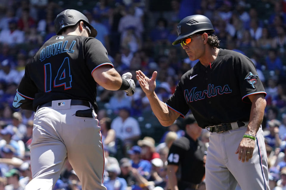Miami Marlins' Adam Duvall celebrates with third base coach Trey Hillman as he rounds the bases after hitting a two-run home run during the first inning of a baseball game against the Chicago Cubs in Chicago, Saturday, June 19, 2021. (AP Photo/Nam Y. Huh)