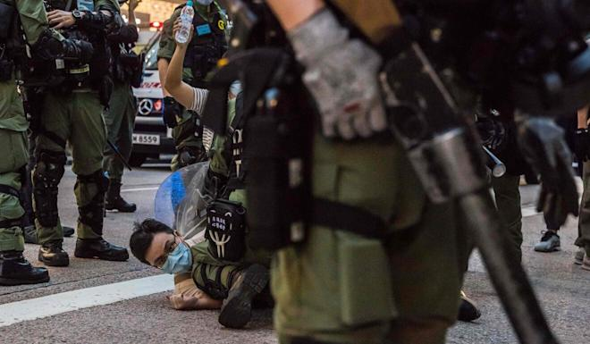 Police detain a man during Sunday's unrest. Photo: AFP