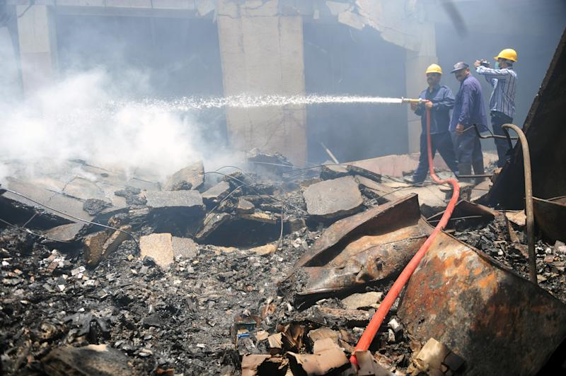 Pakistani firefighters lay water over the smouldering cold-storage facility at the Jinnah International Airport in Karachi on June 11, 2014 (AFP Photo/Rizwan Tabassum)