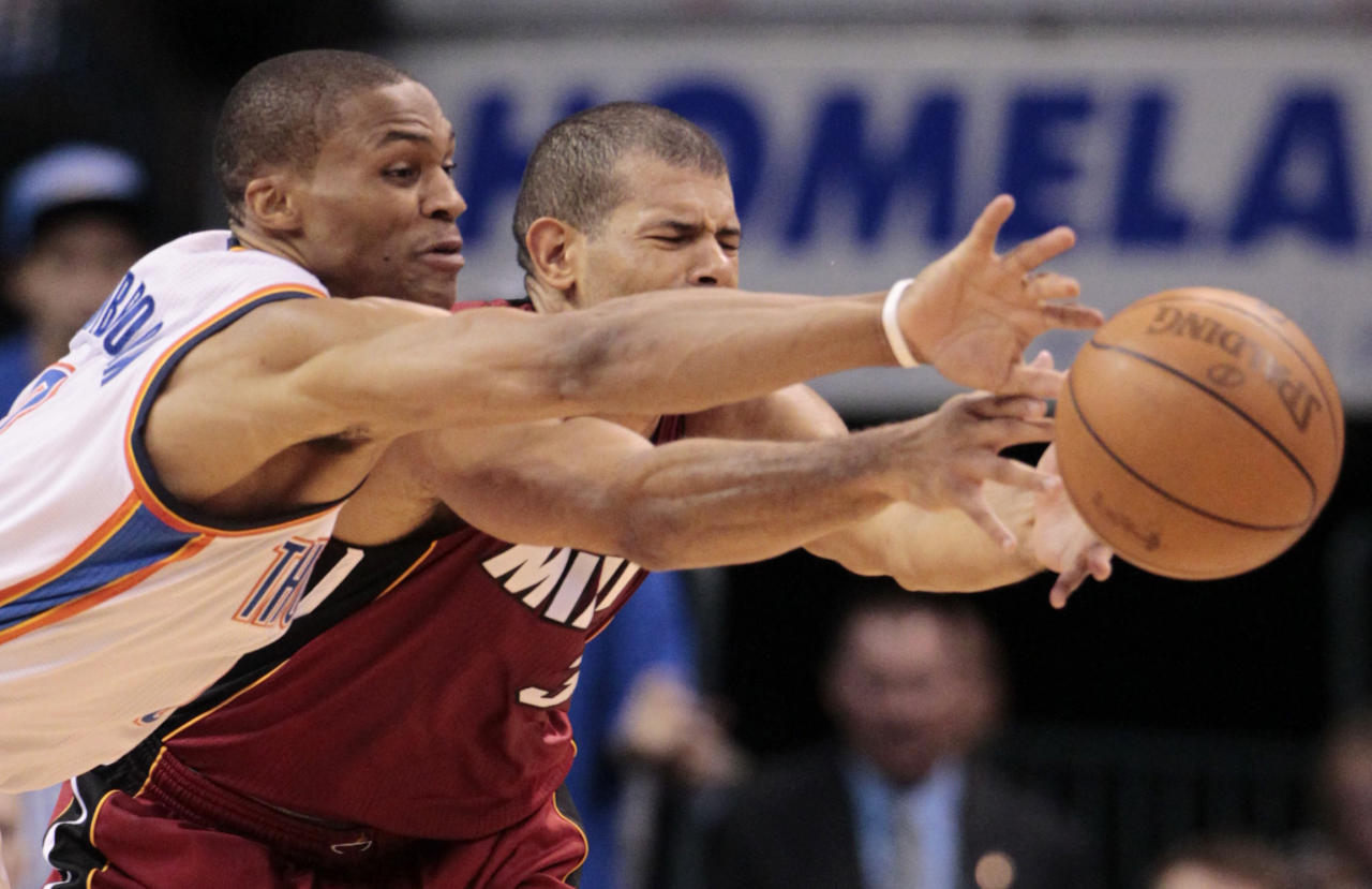 Oklahoma City Thunder point guard Russell Westbrook and Miami Heat small forward Shane Battier go after a loose ball during the first half at Game 1 of the NBA finals basketball series, Tuesday, June 12, 2012, in Oklahoma City. (AP Photo/Jeff Roberson)