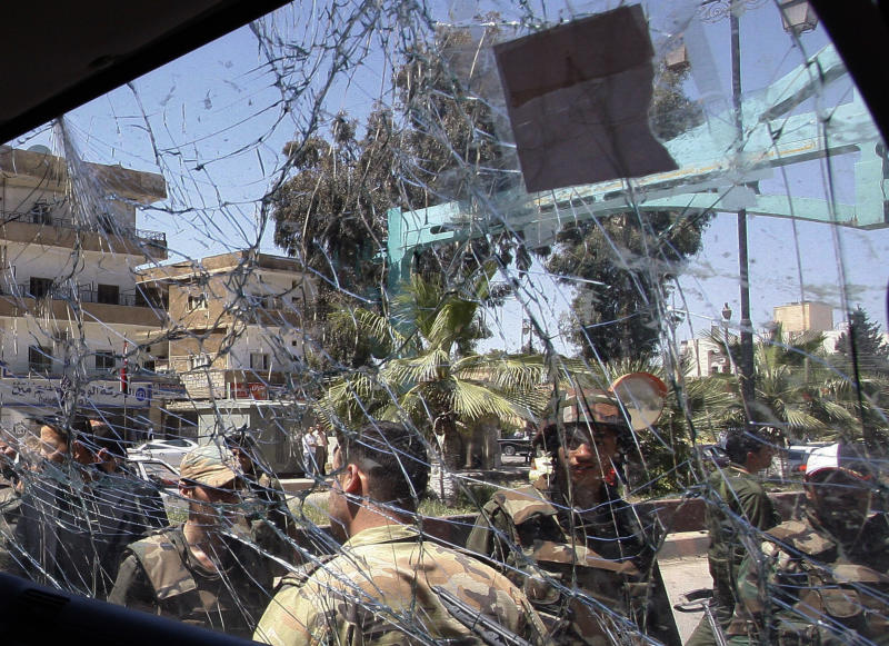Syrian army soldiers, are seen through a damaged military truck window which was attacked by a roadside bomb, in Daraa city, southern Syria, on Wednesday May 9, 2012. The explosion targeted the Syrian military truck just seconds after a team of U.N. observers passed by. An Associated Press reporter who was traveling in the U.N. convoy said three bloodied Syrian soldiers were rushed from the scene after Wednesday's blast, but the U.N. convoy was not hit. (AP Photo/Muzaffar Salman)