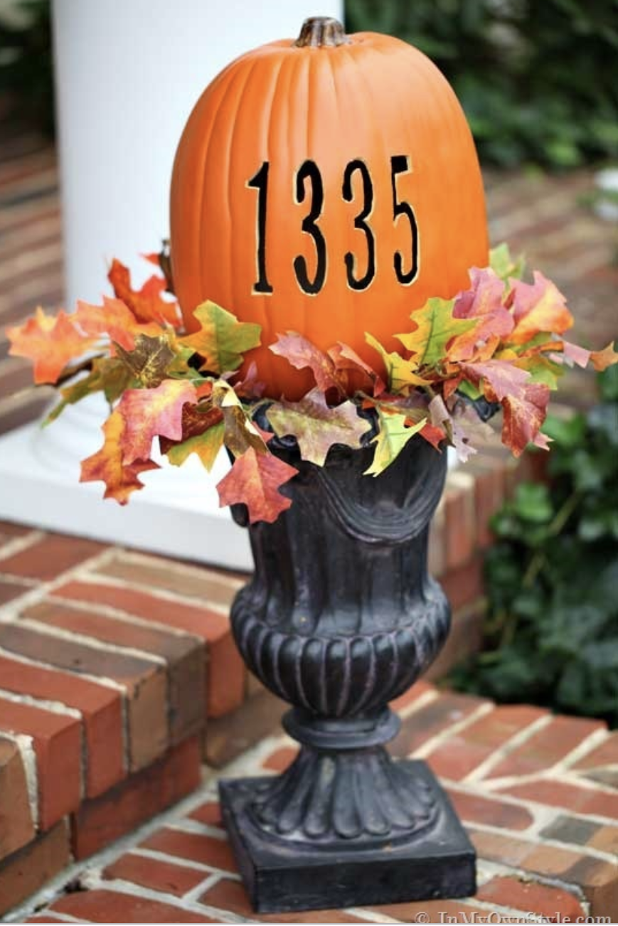 """<p>Put a decorative spin on one of the more utilitarian elements of your porch by carving your house number into a faux pumpkin. </p><p><a class=""""link rapid-noclick-resp"""" href=""""https://inmyownstyle.com/carve-pumpkin-hot-knife.html"""" rel=""""nofollow noopener"""" target=""""_blank"""" data-ylk=""""slk:GET THE TUTORIAL"""">GET THE TUTORIAL</a></p>"""