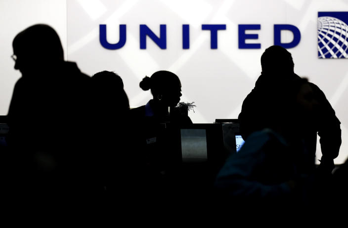 FILE - In this Saturday, Dec. 21, 2013, file photo, travelers check in at the United Airlines ticket counter at Terminal 1 in O'Hare International Airport in Chicago. United Airlines hopes to bring back supersonic travel before the end of this decade. United said Thursday, June 3, 2021 that it reached a deal with startup aircraft maker Boom Supersonic to buy 15 of Boom's Overture jets. (AP Photo/Nam Y. Huh, File)