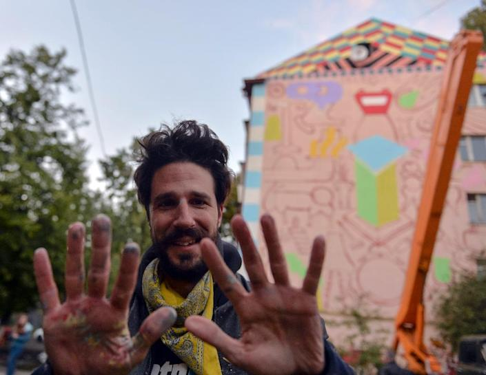 Spanish artist Zosen Bandido poses in front of his unfinished mural on a residential building in Kiev (AFP Photo/Genya Savilov)