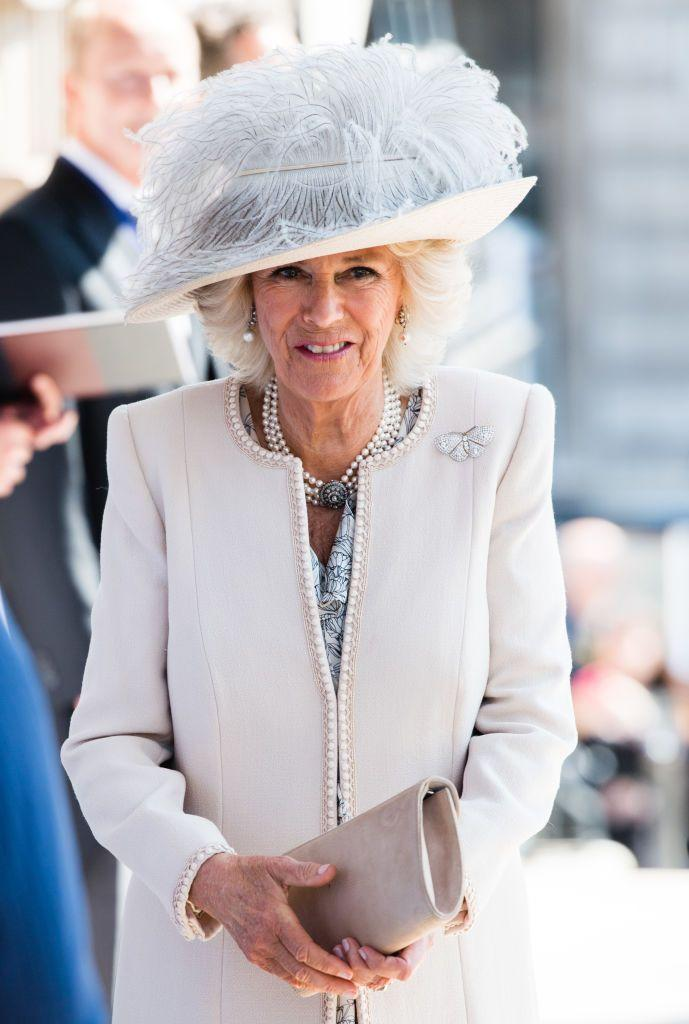 <p>Camilla wore this foggy gray and cream hat, bow brooch, and cream colored coat with pearl edging to an event for the Victoria Cross and George Cross Association in London, England.</p>