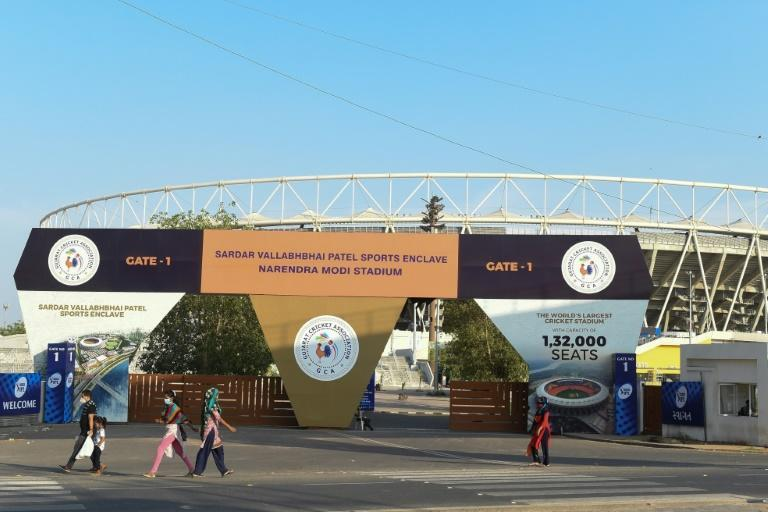 People make their way past the main entrance of the Narendra Modi Stadium, one of the IPL venues, in Motera following decision to suspend the tournament because of coronavirus