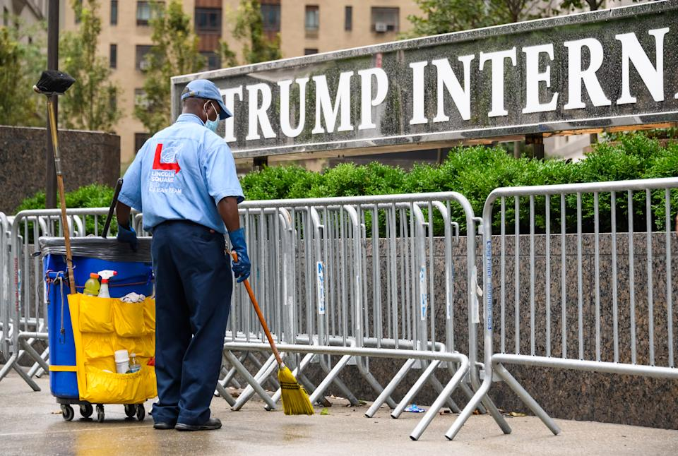 NEW YORK, NEW YORK - AUGUST 16: A sanitation worker cleans outside Trump International Hotel & Tower New York as the city continues Phase 4 of re-opening following restrictions imposed to slow the spread of coronavirus on August 16, 2020 in New York City. The fourth phase allows outdoor arts and entertainment, sporting events without fans and media production. (Photo by Noam Galai/Getty Images)